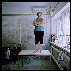 """Алина Нестеровна. """"Петр Остапенко нас спас, с мужем, он залез через чердак на крышу своего дома, прыгнул в воду, во двор, доплыл до нас, хотя течение очень сильное было, муж у меня инвалид сейчас, он бы не выжил... Вот на этом столе мы и стояли. Два часа он Юру держал на руках, потом поплыл к детям... Не доплыл..."""". Ул. Олимпийская, 15"""