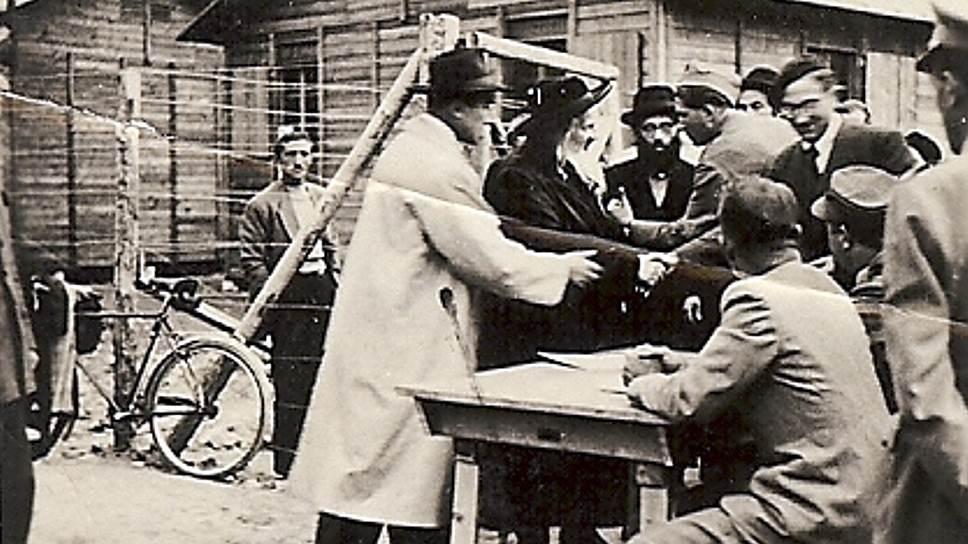 Георг Мандель (первый слева, в белом пальто) уговаривает швейцарских пограничников впустить венгерского раввина, 7 декабря 1944 года