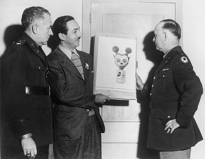 Уолт Дисней (в центре) демонстрирует военным эскиз противогаза в форме Микки-Мауса, 1942