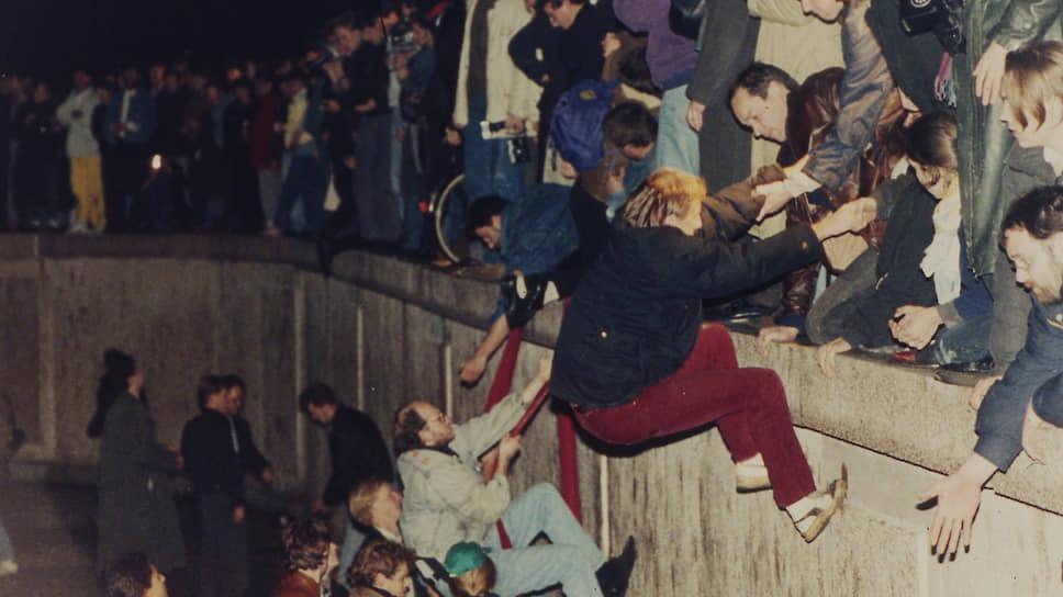 Жители обеих частей Берлина у Берлинской стены в районе Бранденбургских ворот в ночь с 9 на 10ноября 1989