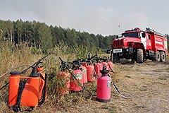 С тлеющими и дымящимися гектарами леса люди могут бороться только с помощью лопат, ведер и песка