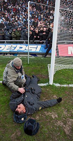НАД СТРАЖЕМ ПОРЯДКАФотограф оказывает медицинскую помощь потерявшему сознание сотруднику милиции на стадионе «Сатурн». Раменское, 2007 год