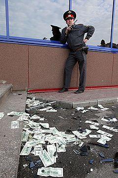 СПАСТИ РЯДОВОГО ФРАНКЛИНАСотрудник милиции и стодолларовые купюры, разбросанные на асфальте после штурма офиса сети гипермаркетов «Лента». Санкт-Петербург, 2010 год
