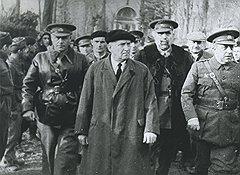 Во время гражданской войны в Испании полководческие таланты Кулика оказались такими же незаметными, как и он сам (на фото — на переднем плане в берете премьер-министр Кабальеро, сзади в кепке — генерал Кулик)