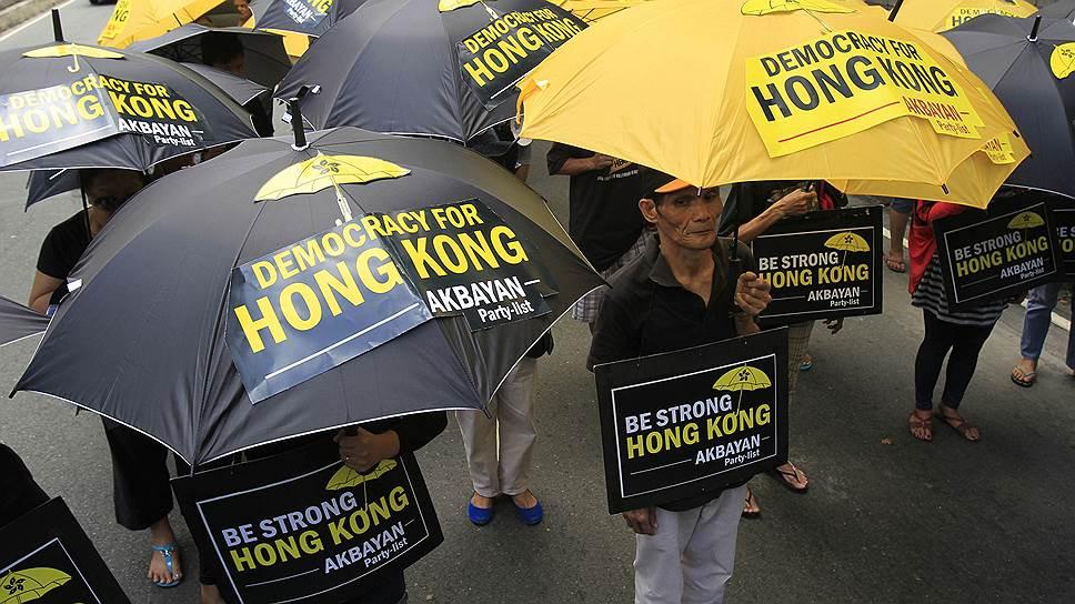 Спасаясь от гранат с газом и баллончиков с перцовым спреем, протестующие использовали зонтики