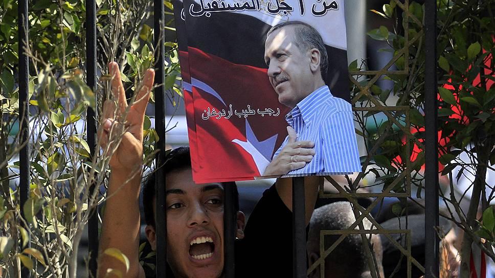 Реджеп Тайип Эрдоган приветствует своих сторонников жестом исламистов