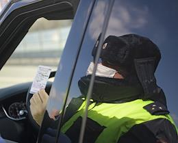 Moscow during self-isolation regime caused by the danger of the coronavirus COVID-19 spread. Genre photography. Surprise check by Road Patrol Service. Road Patrol Service officer checks driver travel permits.