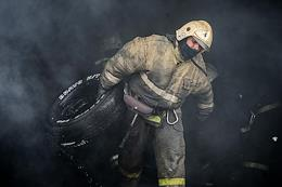 Emergency services officers extinguish a large fire in a warehouse in Novosibirsk.