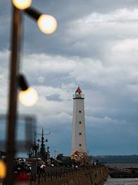 Genre photographs. Views of Kronstadt. Visitors to PKiO Patriot. Walking along the Petrovsky Canal overlooking the lighthouse in the Merchant Harbor.